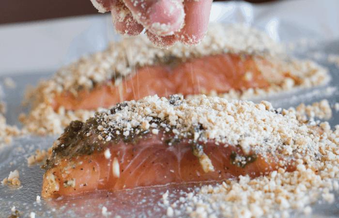 Hand sprinkling chopped cashews on salmon
