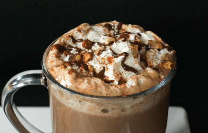 closed up of spiced hazelnut hot chocolate with whip cream and chocolate drizzle
