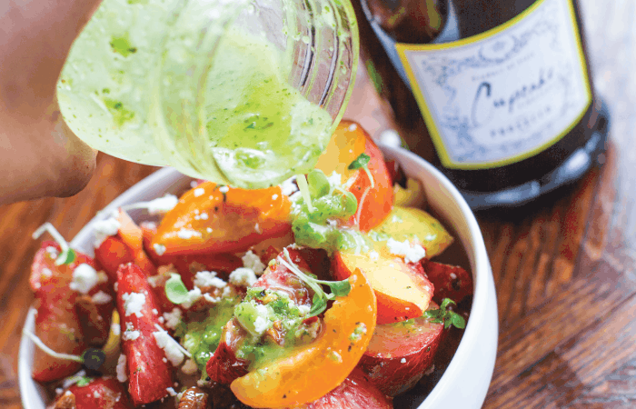 Pouring Jalapeno & Prosecco Vinaigrette over Summer Stone Fruit Salad