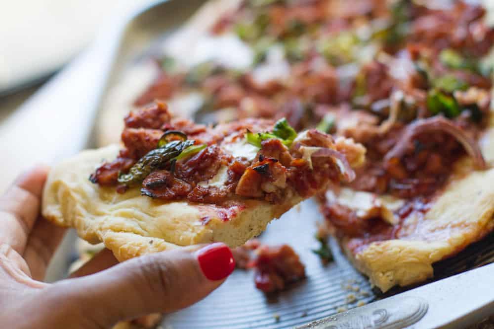 holding slice of Cranberry BBQ Turkey Pizza