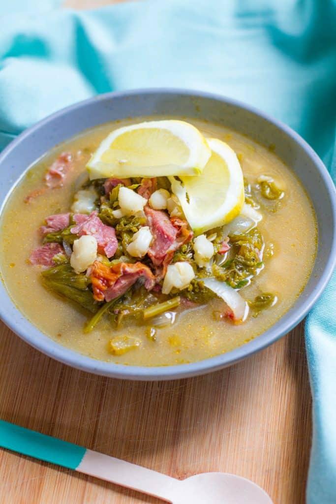Close up bowl of Lemony Southern Style Posole garnished with lemon slices.