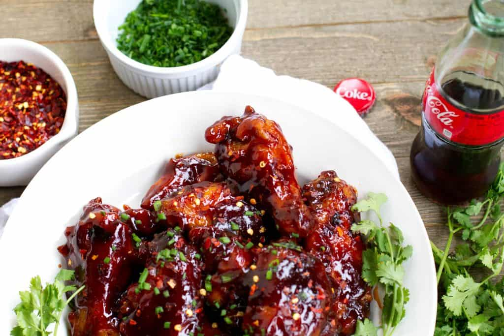 Spicy coca-cola wings on a a plate with a bottle of coke