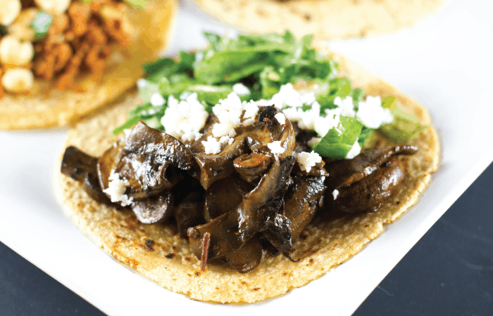 Close up of Chipotle Mushroom Tacos topped with crumbled queso fresco and mesclun greens.