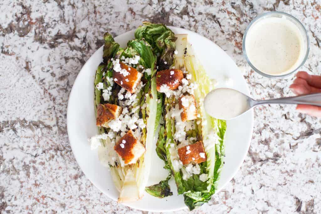 Crispy grilled romaine drizzled with a homemade smoky Caesar dressing totally elevates the traditional Caesar salad.