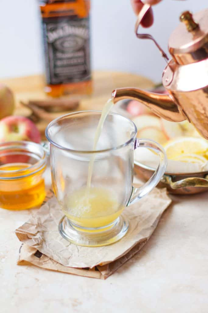 View of pouring warm apple cider from a copper tea kettle into a glass mug. With surrounding ingredients in the background honey, lemons, apples, whiskey.