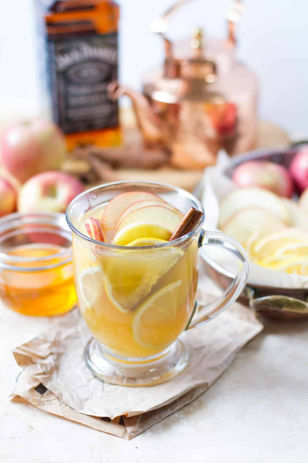 Portrait image of hot zaddy cocktail in glass mug with apple and lemon slices and a cinnamon stick. Surrounded by ingredients.