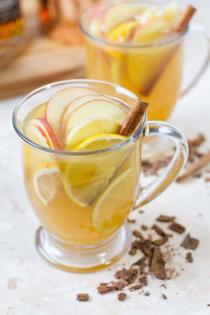 Aerial View of Hot Zaddy - a warm cocktail in a glass mug with slices of lemons, apples and a cinnamon stick. With crumbled cinnamon sticks garnished around.