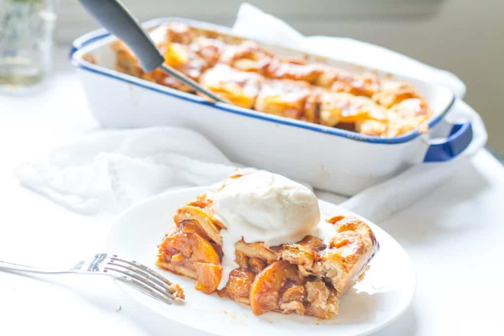 slice of Candied Bourbon Peach Cobbler topped with ice cream