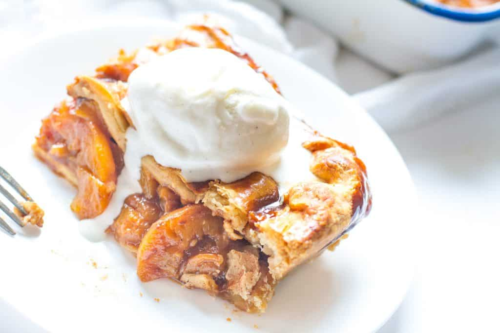 close up slice of Candied Bourbon Peach Cobbler topped with ice cream