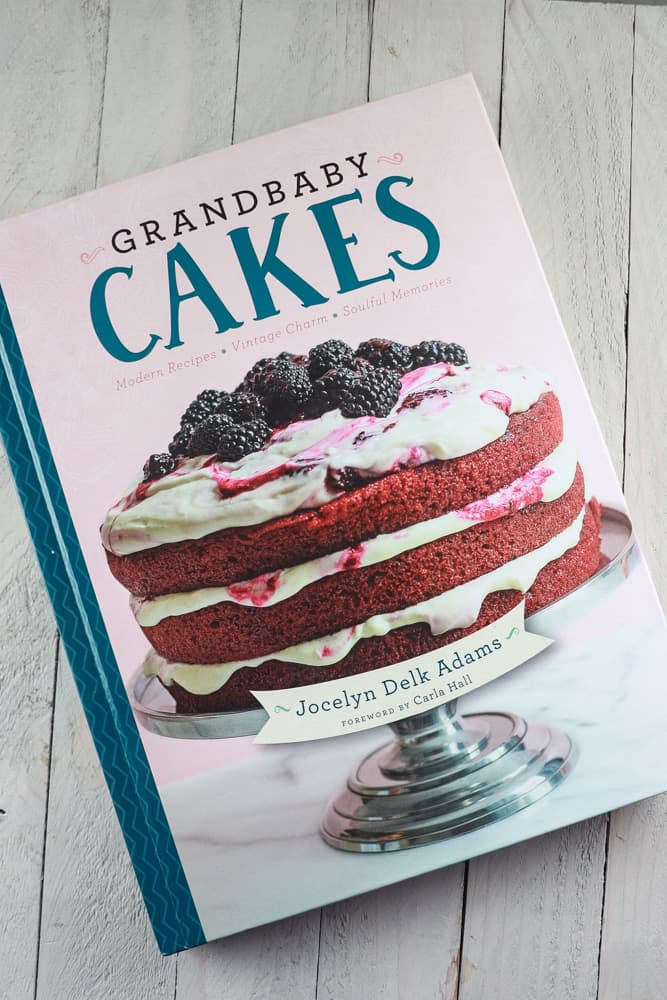 Front cover of GrandBaby Cakes Cook book with a 3 tier red velvet cake and black berries.