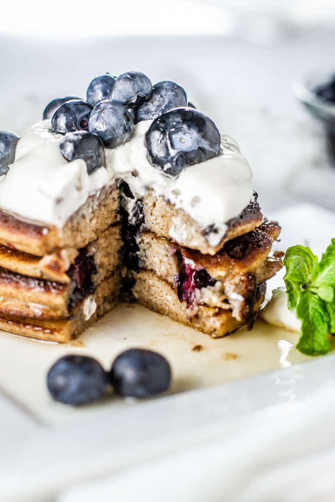 Cut into a stack of Blueberry Lemon Keto Pancakes topped whipped cream and fresh blueberries.