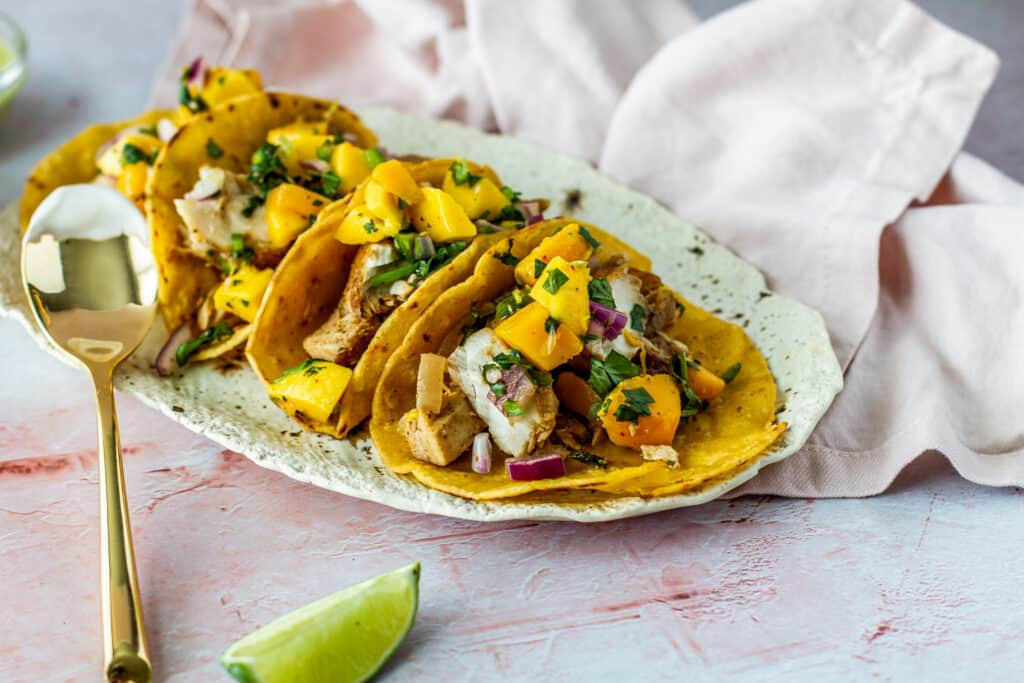 Three Spicy Citrus Fish Tacos with Mango Salsa on serving tray with a lime wedge.