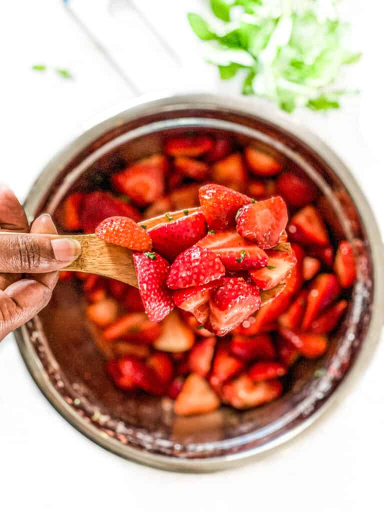 Combination of sliced strawberries and julienned mint on a wooden cooking spoon.