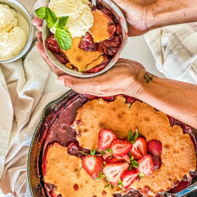 Strawberry Cornbread Skillet Cobbler being served topped with ice cream and garnish with mint leaves.