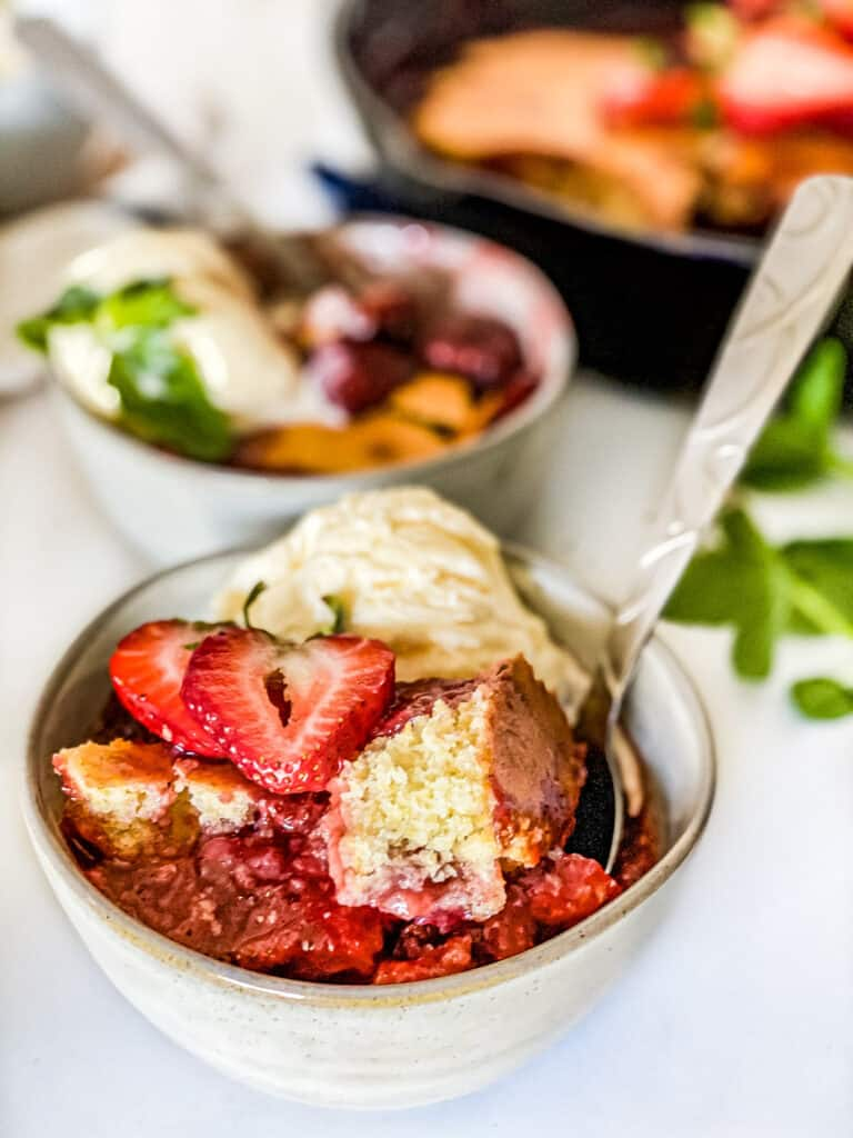 Close up of Strawberry Cornbread Skillet Cobbler in a bowl topped with ice cream