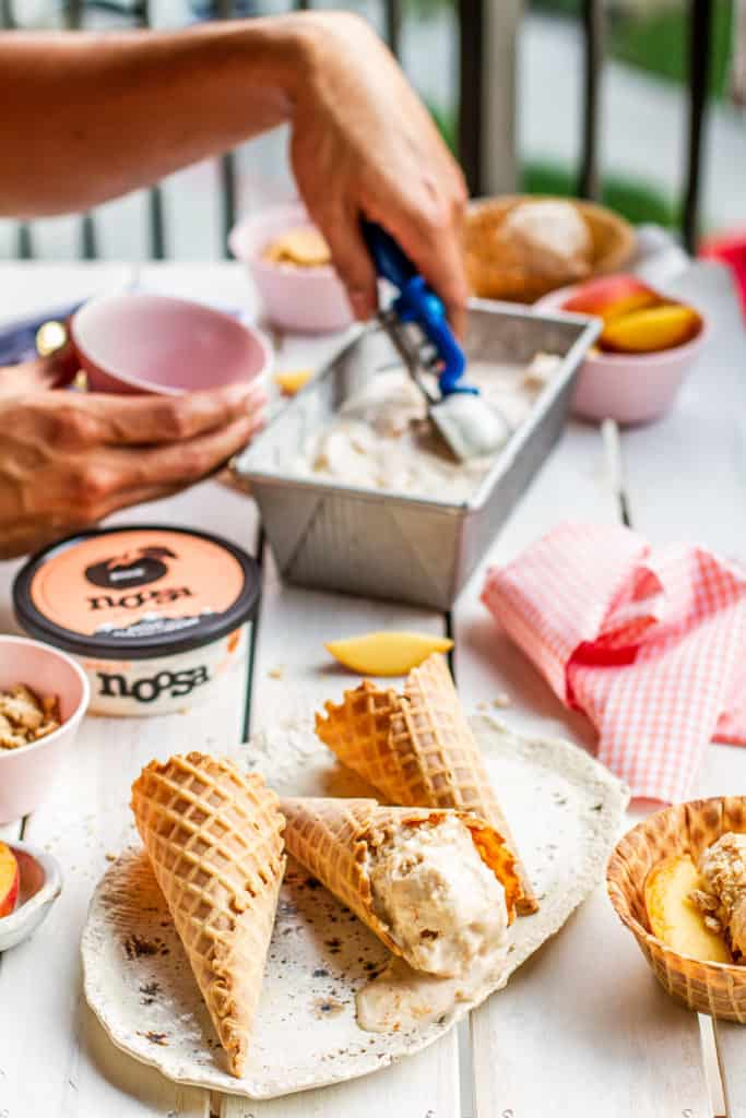 hand scooping peach frozen yogurt in a waffle cone on a picnic table