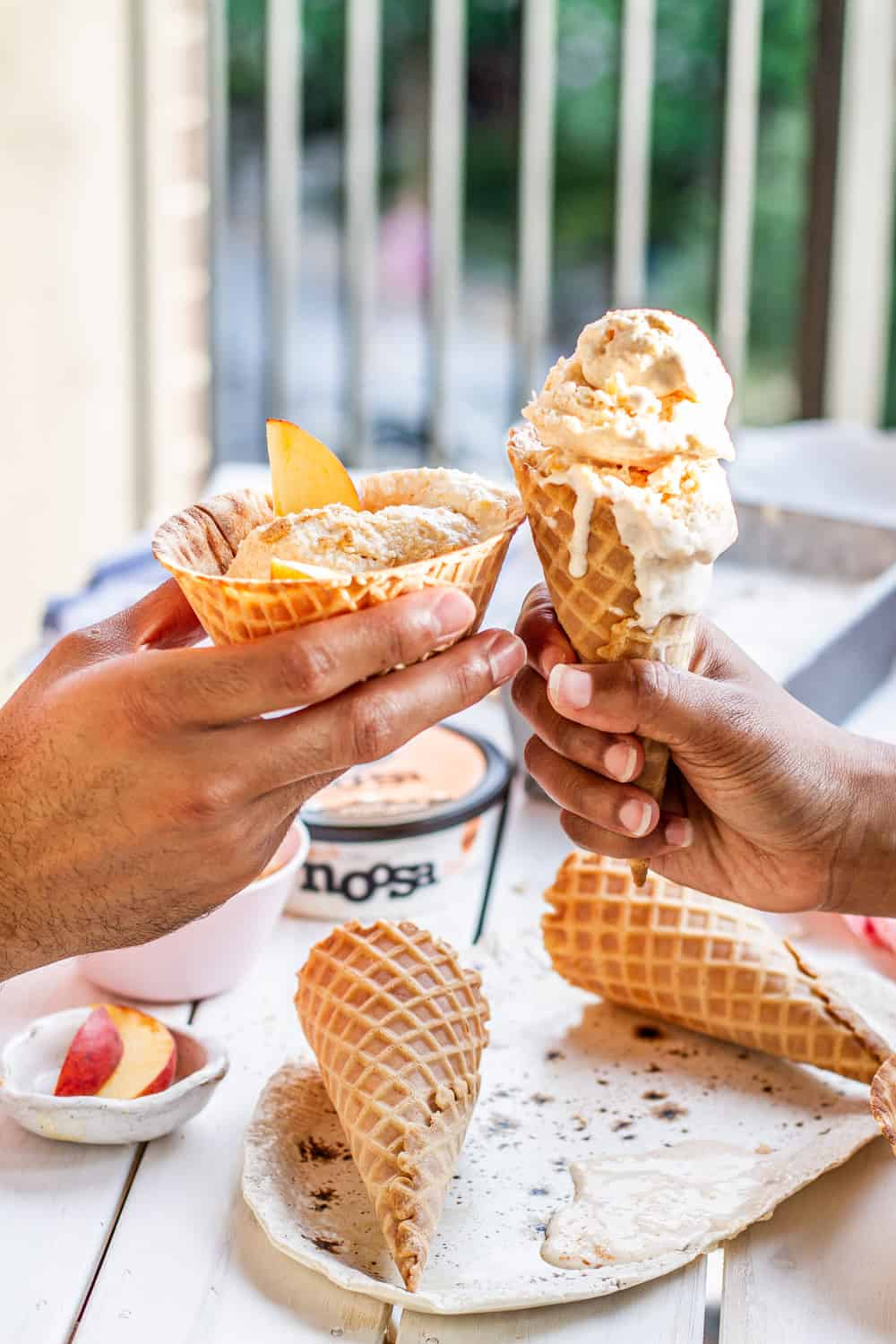 hands holding peach frozen yogurt in a waffle cones on a picnic table