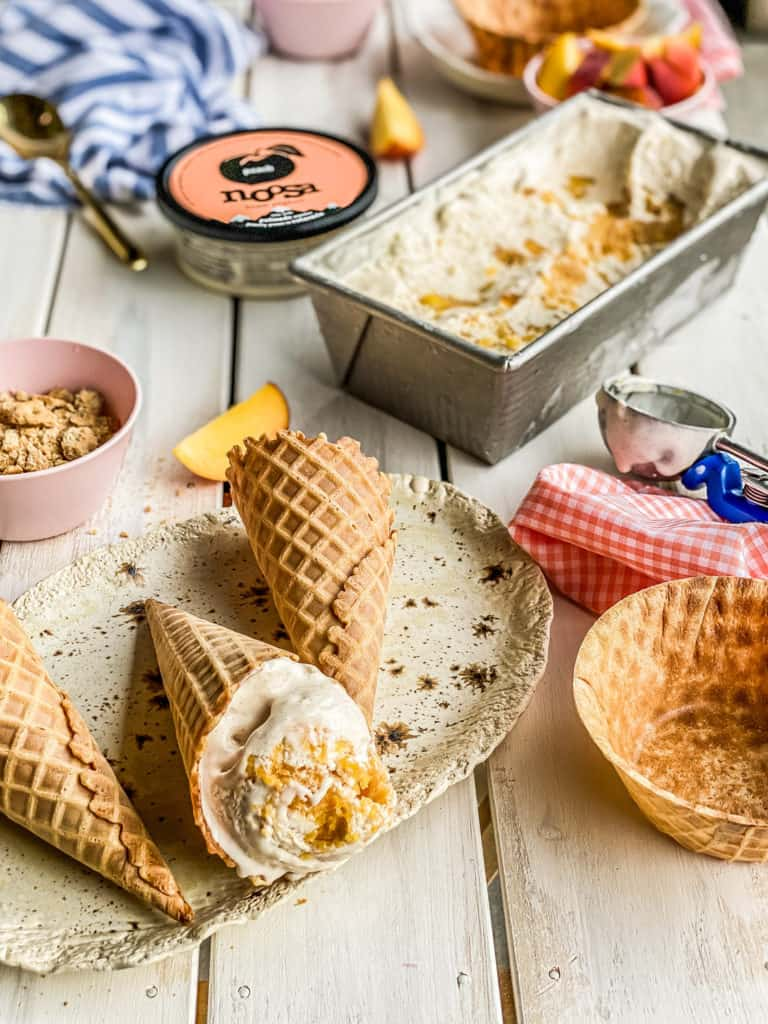 peach frozen yogurt in a waffle cone on a picnic table