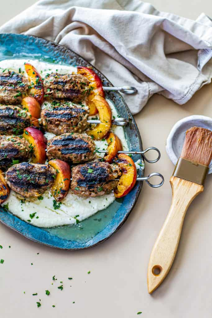 turkey kefta & peach kabobs on top of whipped feta with a brush