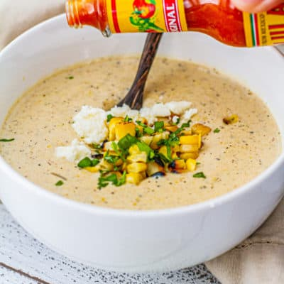 Pouring hot sauce on elote corn chowder