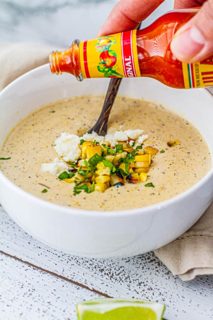 Pouring hot sauce on elote corn chowder in a bowl