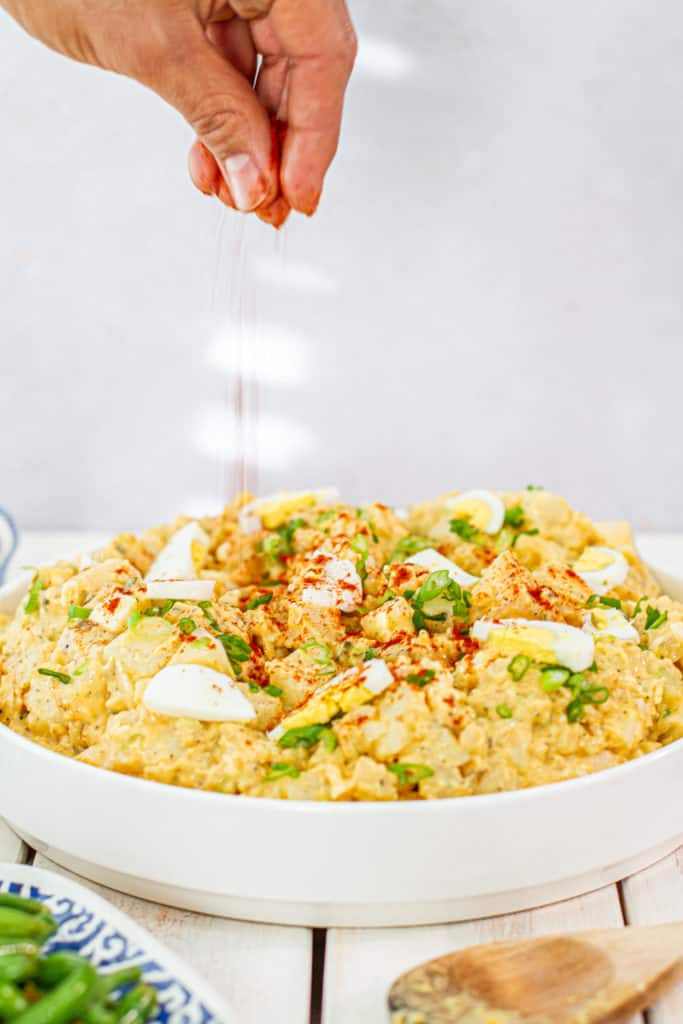 sprinkling paprika on Southern Potato Salad