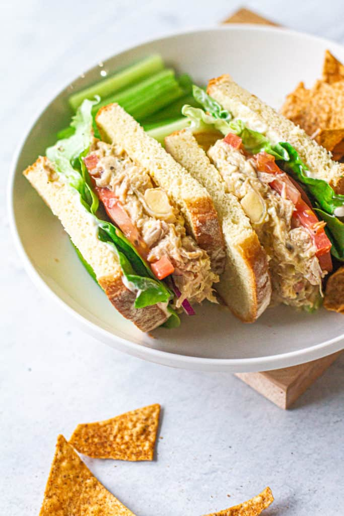 close up of chicken salad sandwich with lettuce, tomato and red onion