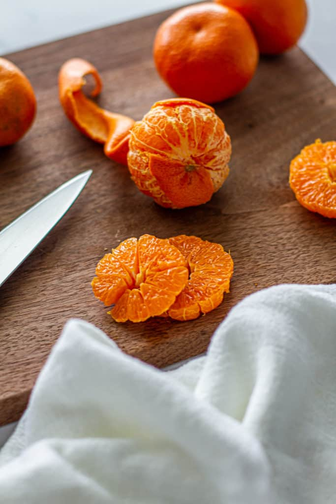 partially peeled clementines on cutting board for detox glow bowl