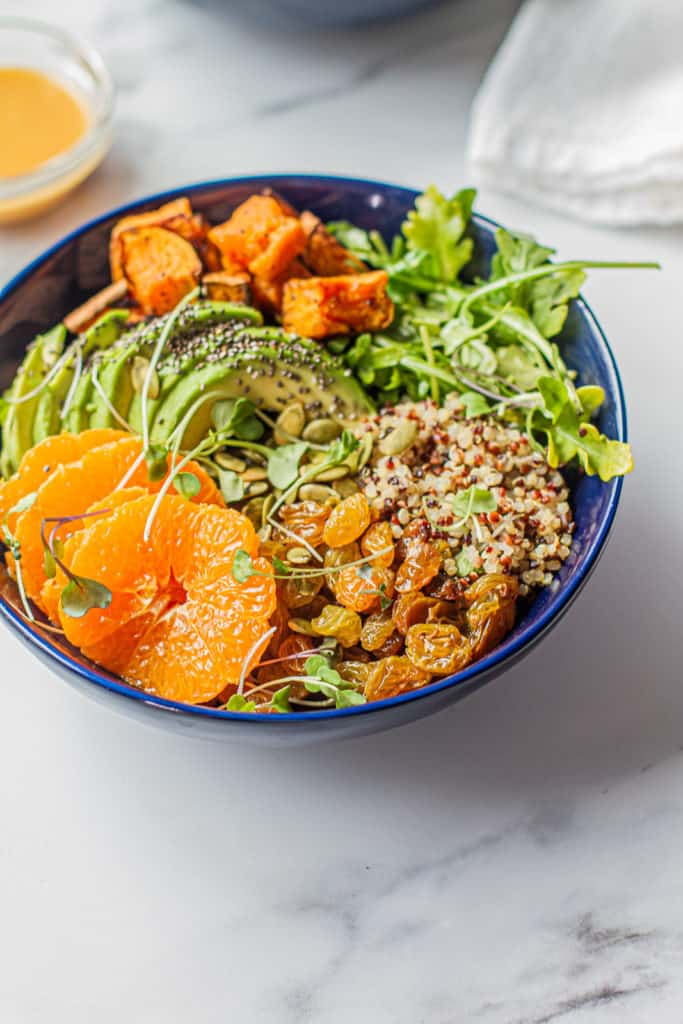 Detox Glow Bowl with clementines, avocado, sweet potatoes, arugula, quinoa, golden raisins