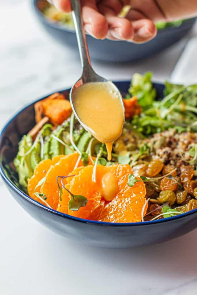 drizzling clementine miso vinaigrette on detox glow bowl