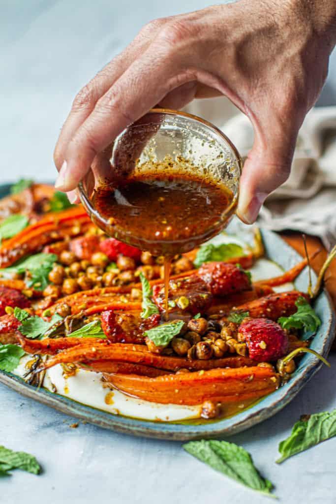 hand pouring ras el hanout vinaigretter over roasted vegetable salad