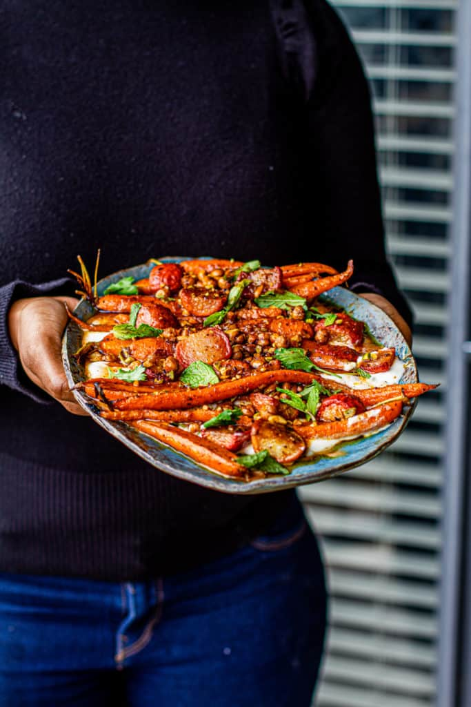 hands holding Platter with moroccan-spiced carrot & radish salad