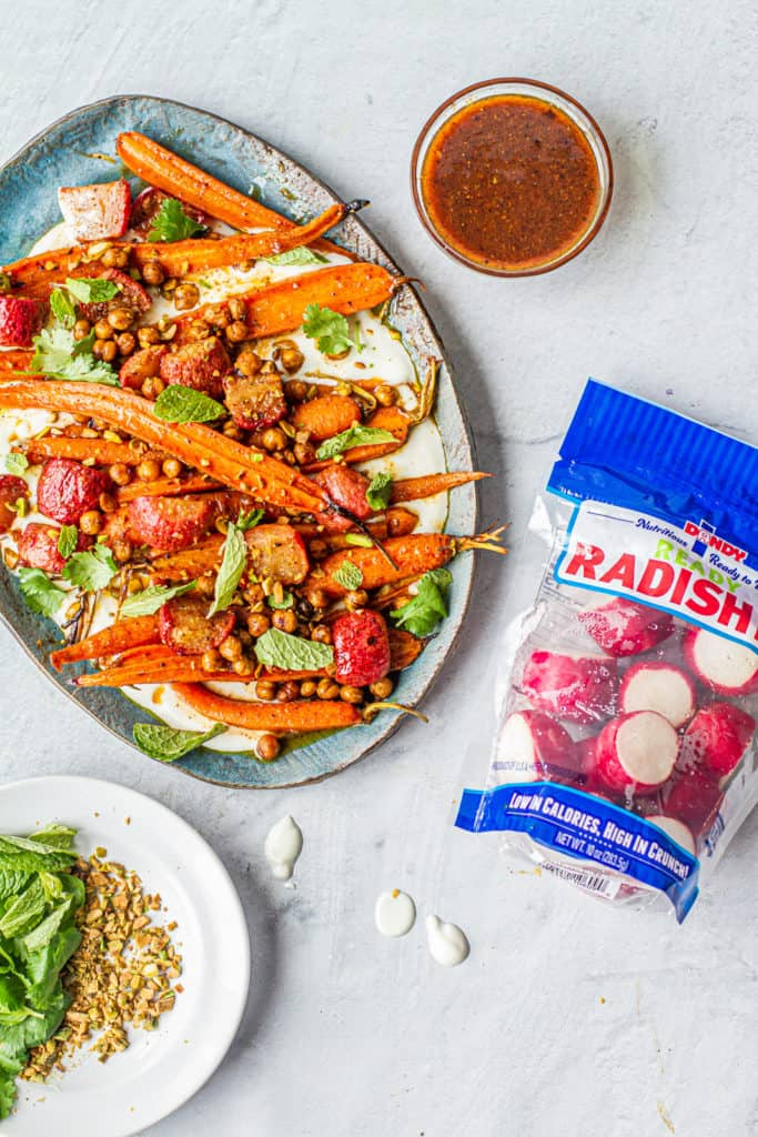 Platter with moroccan-spiced carrot & radish salad next to bag of dandy ready radishes