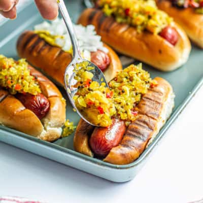 This is a recipe for chow chow and grilled hot links. It shows how to make grilled hot links & homemade chow chow. A hand is adding Southern chow chow relish to hot link on a grilled bun for a Juneteenth celebration..