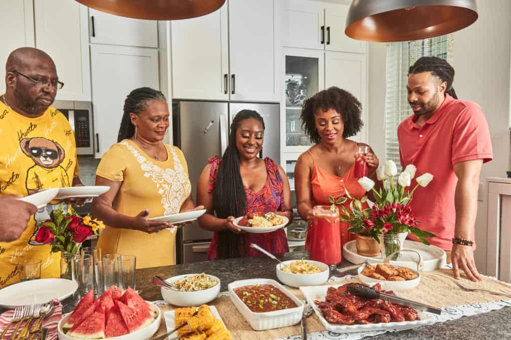 Meiko & Kenneth in the kitchen will family in front of a large spread of Juneteenth foods.