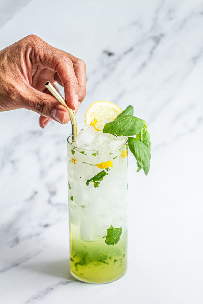 hand placing staw in cup of lemon basil mojito