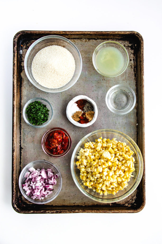 corn salsa ingredients on sheet pan, corn, red onion, spices, calabrian peppers, white wine vinegar, cilantro, lime juice and granulated sugar