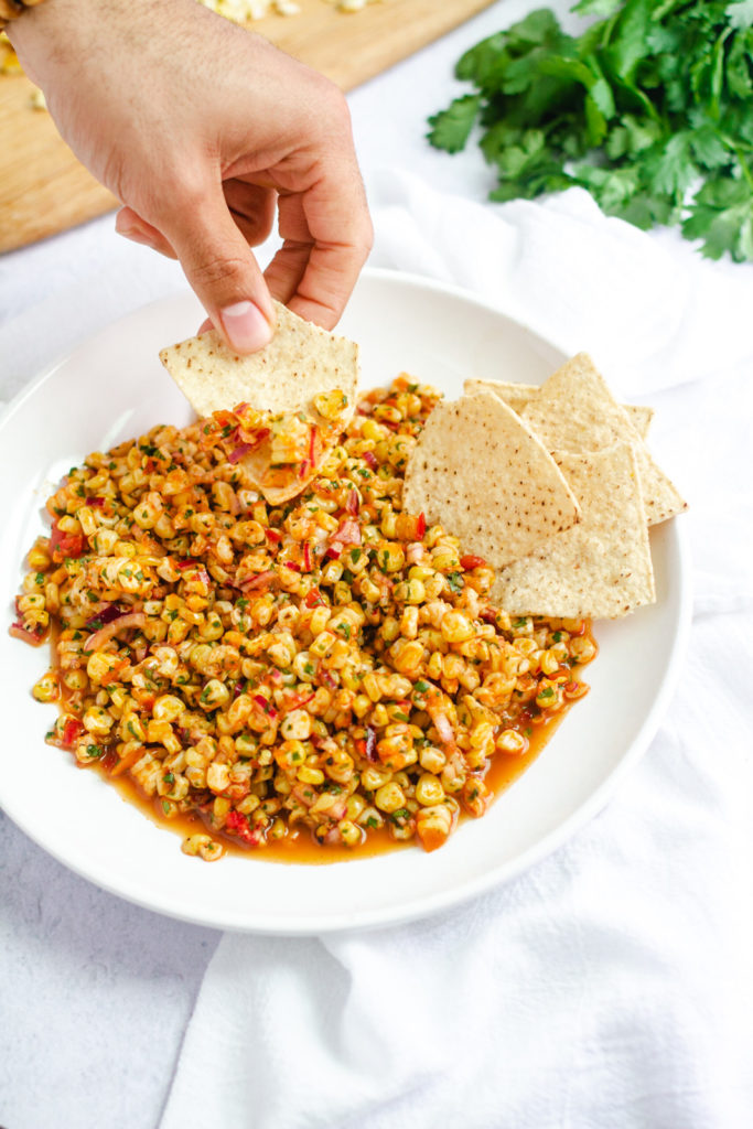 hand with tortilla chip dipping into corn salsa