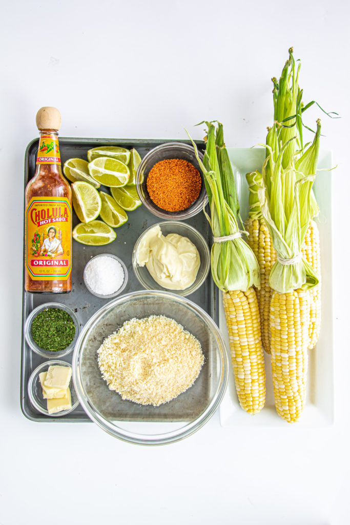 the elote ingredients to make mexican street corn - cotija, butter, cilantro, salt, mayonaise, corn, limes, tajin, hot sauce