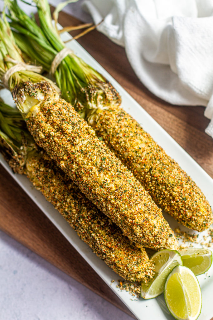 Elote, mexican street corn on a platter with limes