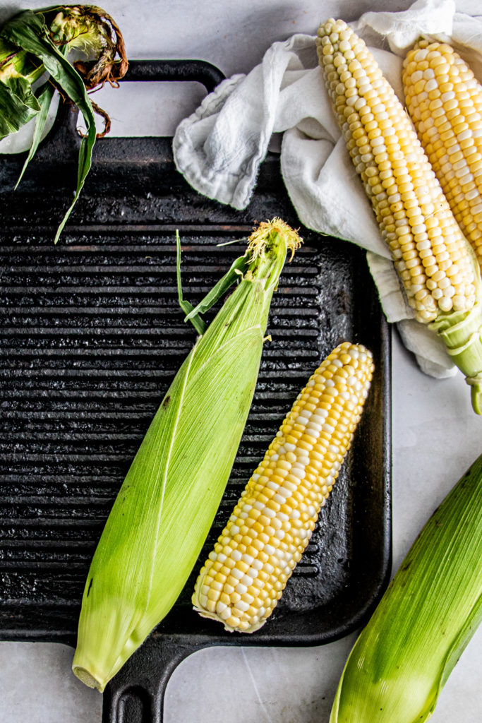 An ear of corn and corn on the cob on a grill pan