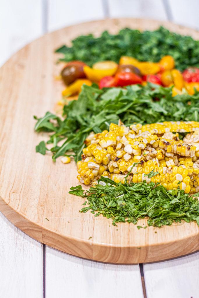 chopped summer vegetables - cilantro, corn, arugula, cherry tomatoes, parsley