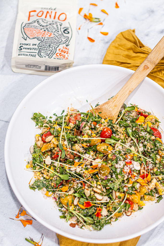 large bowl of summer vegetable & fonio salad next to a package of Yolele fonio