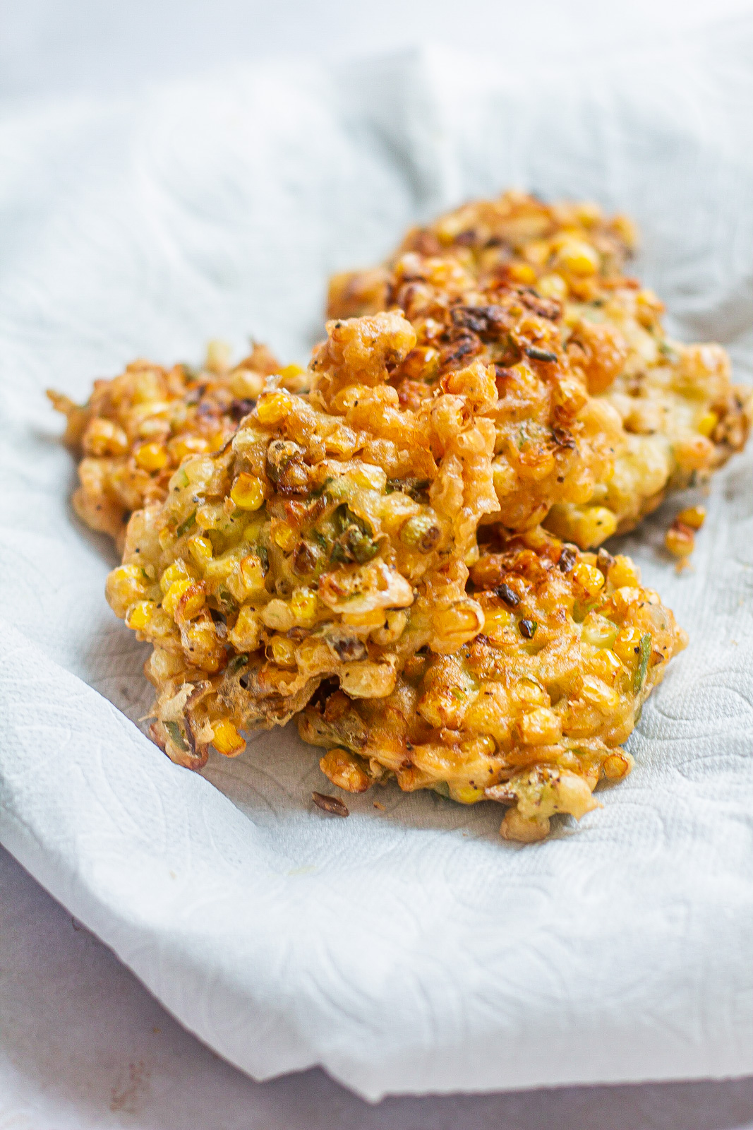 golden corn fritters on a paper towel lined dish