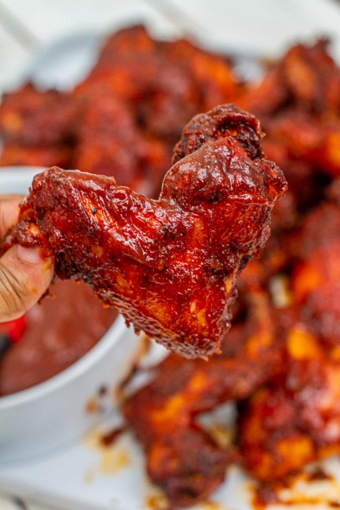 hand holding a kansas city bbq chicken wing