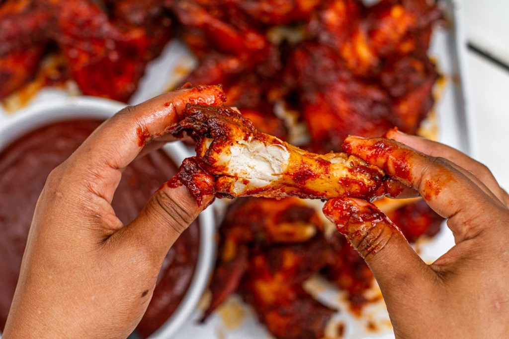 messy hands holding a kansas city bbq chicken wing