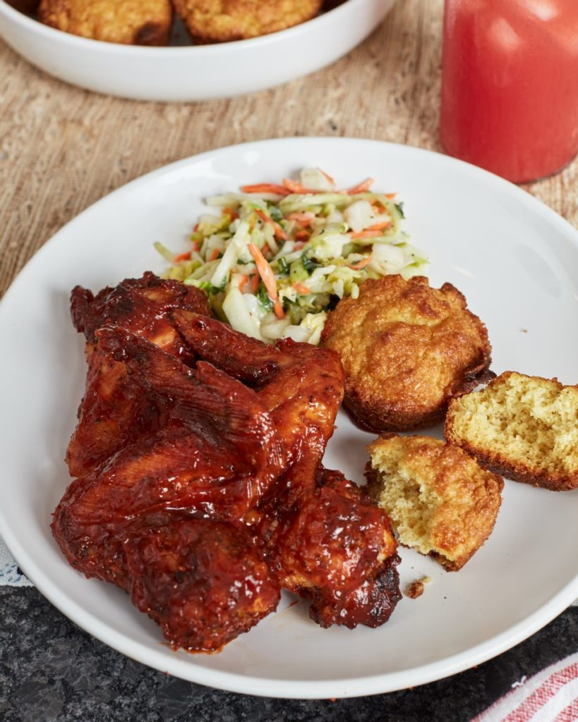plate of food with kansas city bbq wings, cornbread and coleslaw