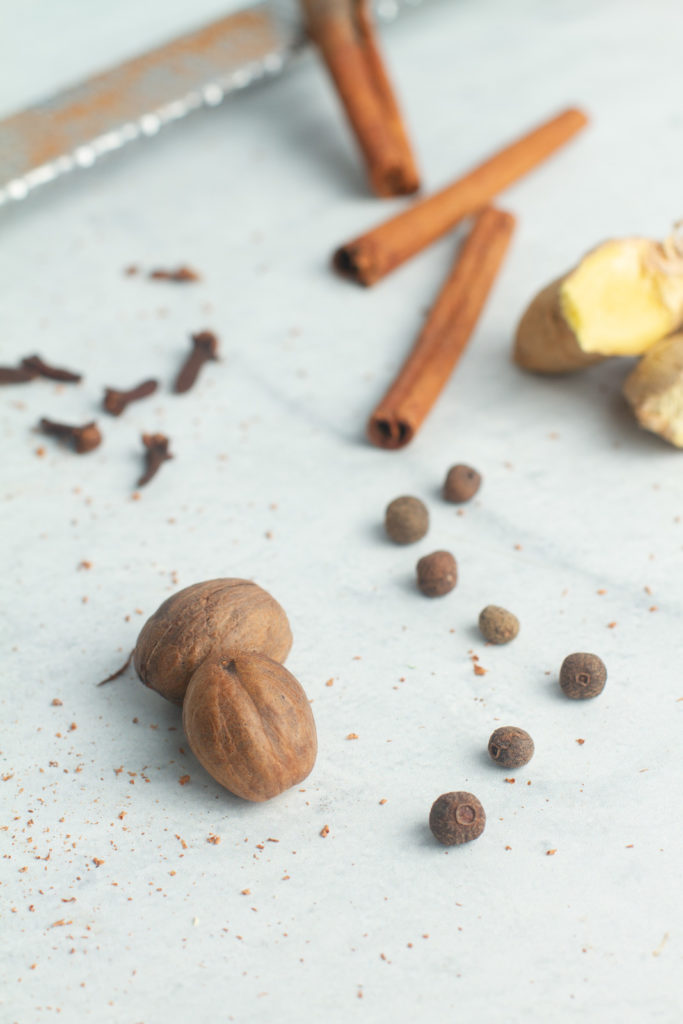 Raw pumpkin spice ingredients whole nutmeg, whole allspice cloves, cinnamon sticks, whole ginger, whole cloves