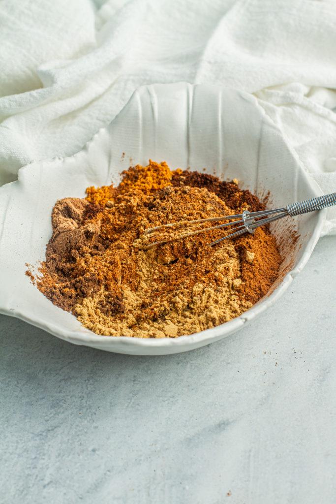 stirring homemade pumpkin spice in a bowl